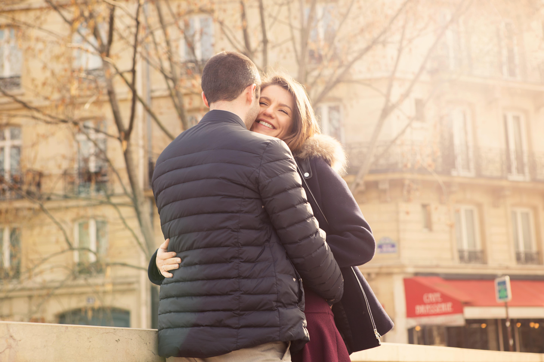 seance photo couple en bord de seine à Paris avec en arrière plan une brasserie et un immeuble haussemanien