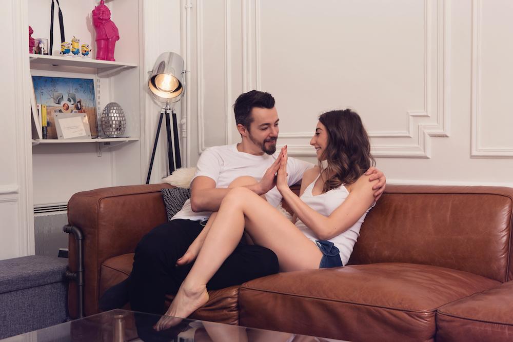 photo d'un couple a Paris dans leur appartement sur un canapé